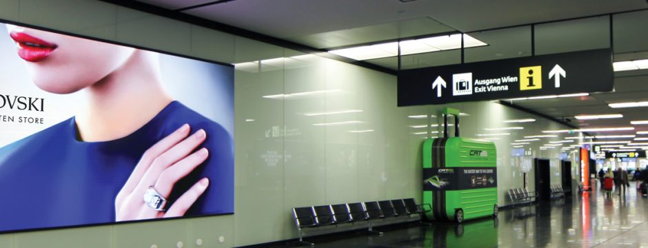 Videowall Flughafen Wien Ankunftshalle mady by firstSpot VIDEOWALLS. SMD Indoor Advertising Display Screen airport Vienna arrival made by firstSpot Österreich.